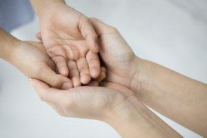 Overlapping hands of women and children