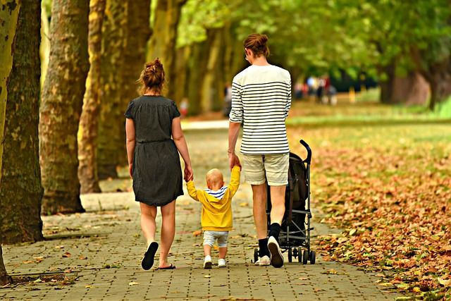 Couple walking with their baby while hold the baby's hands