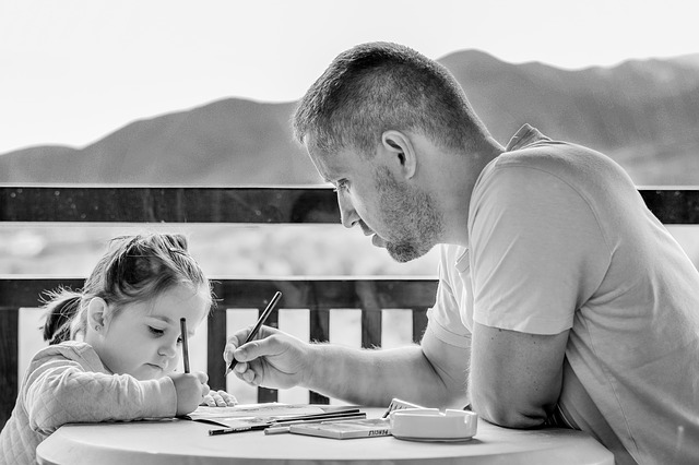 Father and daughter are drawing on paper together