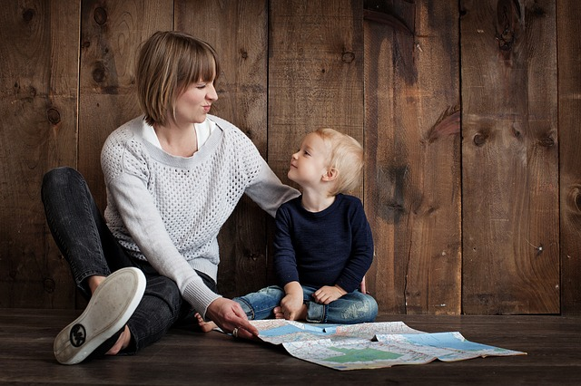 Mother and son are both looking at a map sitting on the floor