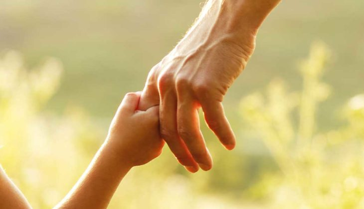 A picture of a girl holding her dad's finger