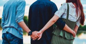 A man holding his male friend, girl friend hand.